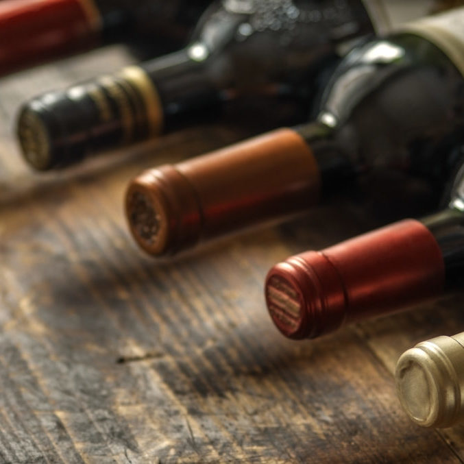 Row of wine bottles with dry red  wine on wooden background. Low depth of field. Wine making and wine shop concept.